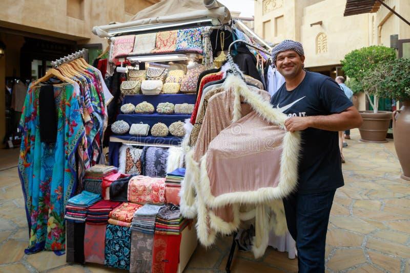 De vriendschappelijke verkoper toont de kwaliteit van de aangeboden goederen stock fotografie