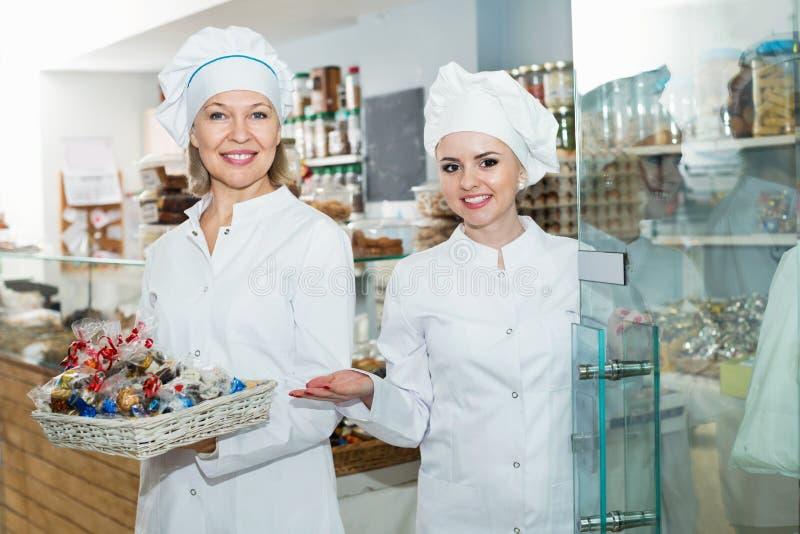 De vriendschappelijke vrouwelijke cliënten van de personeelsgroet in banketbakkerij royalty-vrije stock fotografie