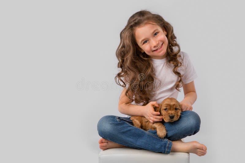 De vriendschapsconcept van het jonge geitjeshuisdier - meisje met rood die puppy op witte achtergrond wordt geïsoleerd stock foto