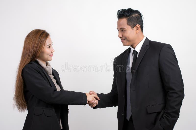 De vrij Aziatische zakenman van onderneemster schuddende handen om te verzegelen behandelt zijn partner op een witte achtergrond stock afbeelding