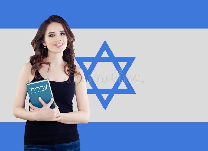De vrij donkerbruine studente met de vlag van Israël, bestudeert Hebreeuws taalconcept stock afbeelding