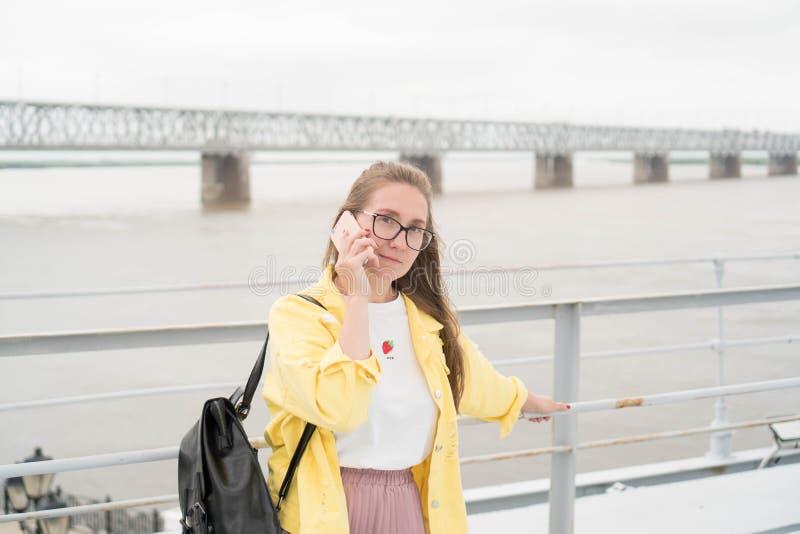 De vrij Europese vrouw in een geel denimjasje spreekt ernstig op de telefoon tegen de achtergrond van de rivier Portret van stock afbeeldingen