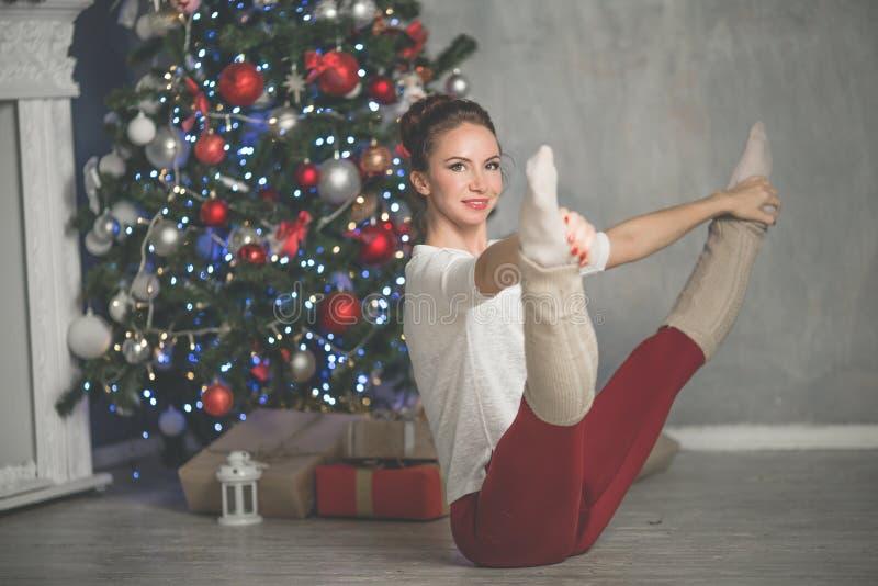 De vrij flexibele jonge vrouw doet sporten dichtbij Kerstmisboom, sporten en vakantieconcept royalty-vrije stock foto's