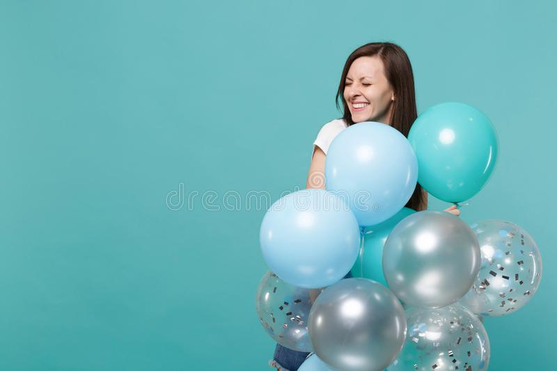 De vrij glimlachende jonge vrouw in denimkleren die ogen houden sloot, het vieren, houdend kleurrijke luchtballons geïsoleerd  stock afbeeldingen
