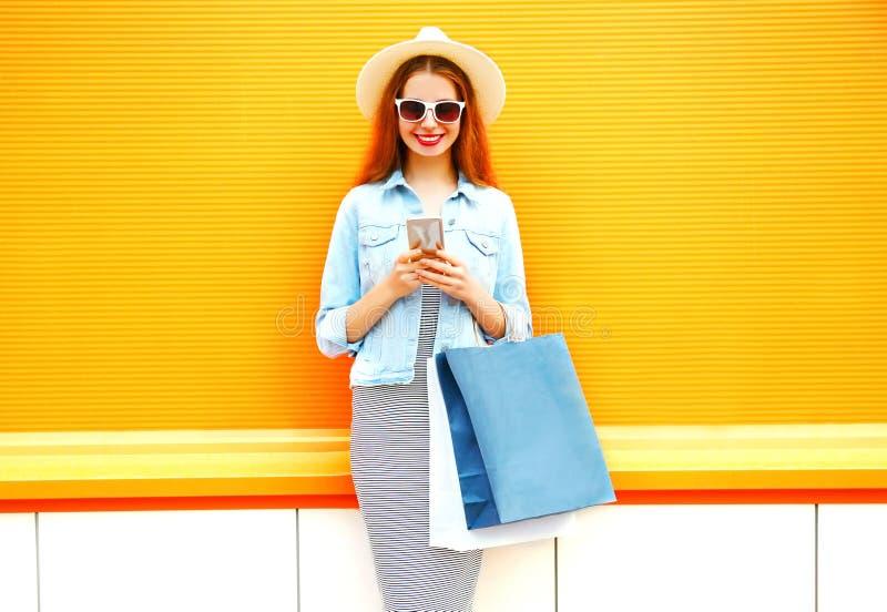 de vrij glimlachende jonge vrouw gebruikt smartphone in de stad stock afbeelding