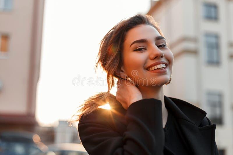 De vrij grappige jonge vrouw in een zwarte uitstekende T-shirt in een in zwarte laag geniet van een oranje heldere zonsondergang  stock afbeeldingen