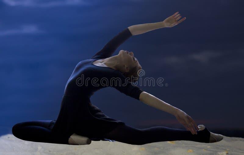 De vrij jonge bevallige balletdanser warmt op een zandig strand op stock afbeelding