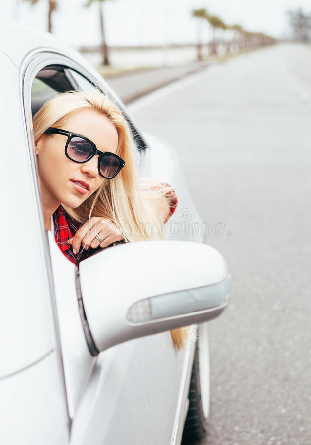 De vrij jonge blondevrouw kijkt uit van autoraam stock afbeeldingen