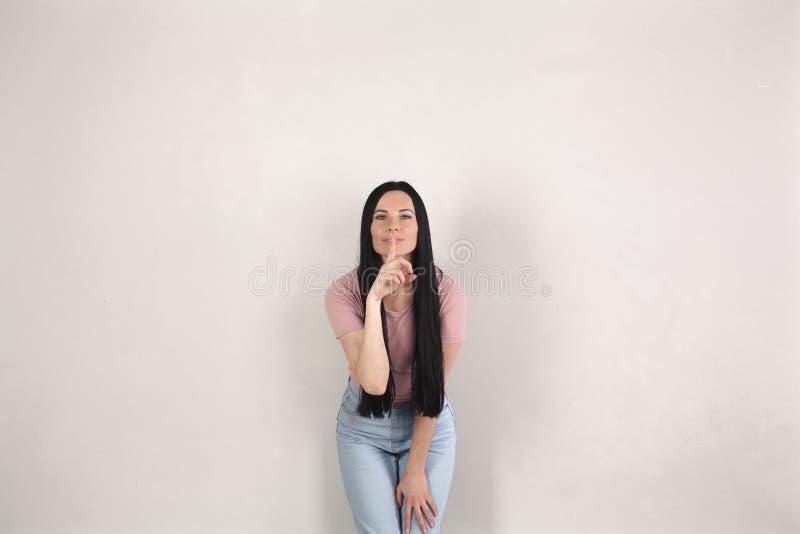 De vrij jonge donkerbruine vrouw met lang haar bevindt zich door de grijze achtergrond die vooruit en stilteteken met het buigen  stock fotografie