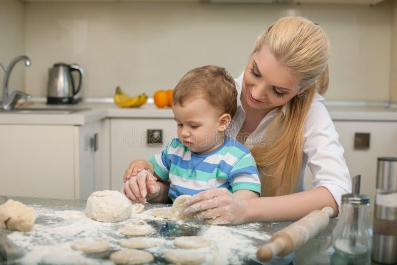 De vrij jonge huisvrouw kookt met haar kind royalty-vrije stock foto