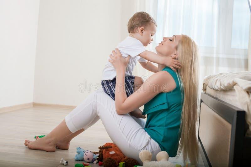 De vrij jonge moeder omhelst haar kind stock foto