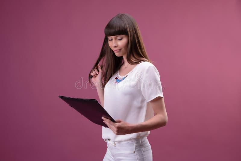 De vrij jonge mooie vrouw status, die neemt nota's, die handboekorganisator en pen in hand houden schrijft royalty-vrije stock foto