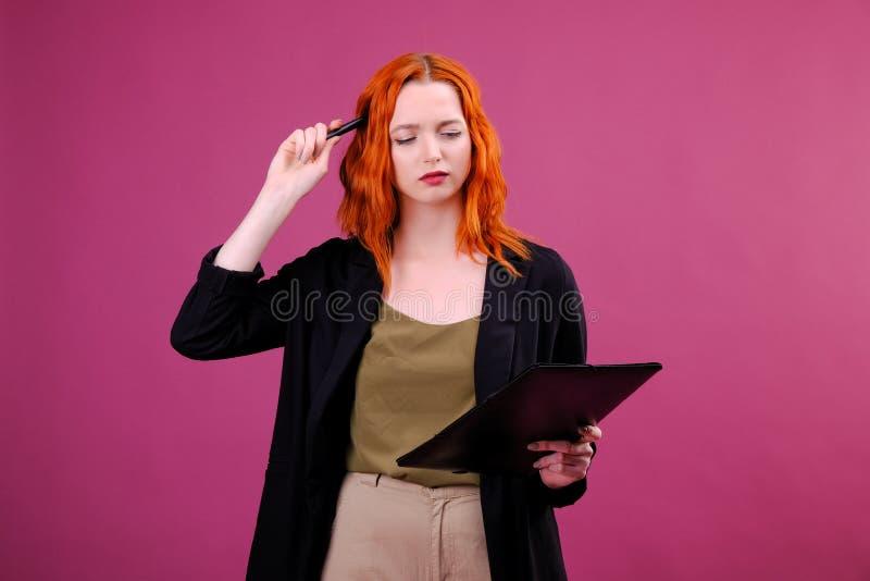 De vrij jonge mooie vrouw status, die neemt nota's, die de organisator van het handboeknotitieboekje en pen in hand houden schrij royalty-vrije stock afbeeldingen