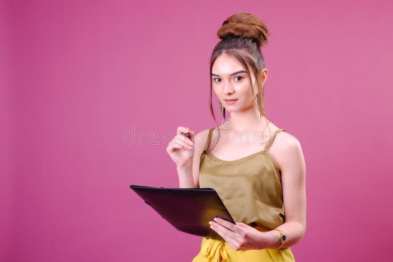 De vrij jonge mooie vrouw status, die neemt nota's, die de organisator van het handboeknotitieboekje en pen in hand houden schrij stock foto