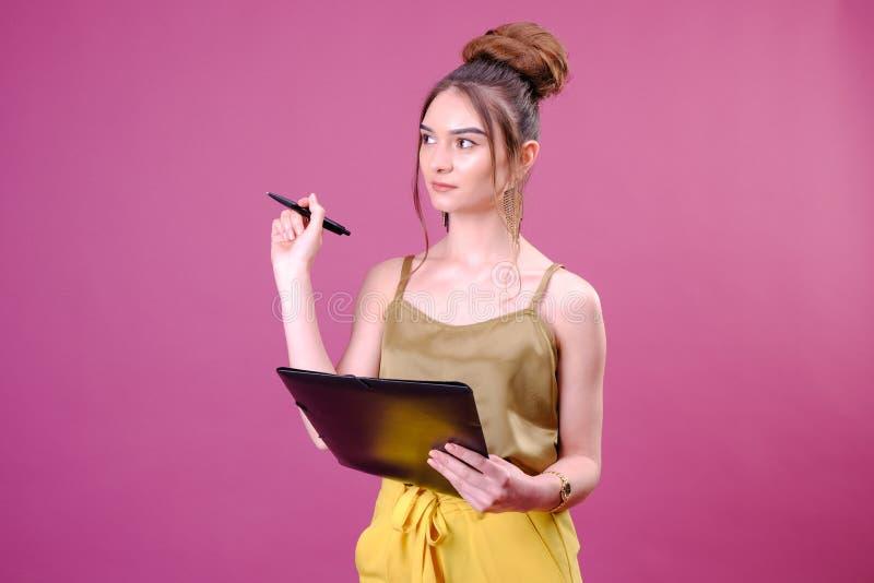 De vrij jonge mooie vrouw status, die neemt nota's, die de organisator van het handboeknotitieboekje en pen in hand houden schrij royalty-vrije stock foto's