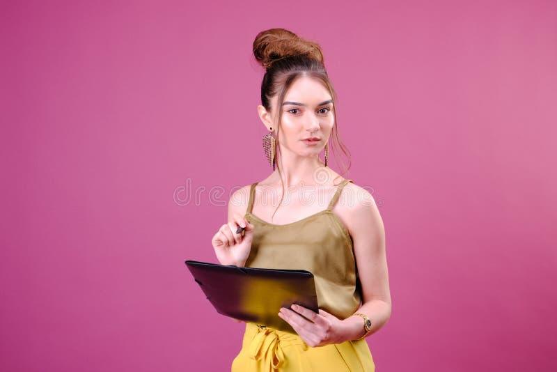 De vrij jonge mooie vrouw status, die neemt nota's, die de organisator van het handboeknotitieboekje en pen in hand houden schrij royalty-vrije stock fotografie