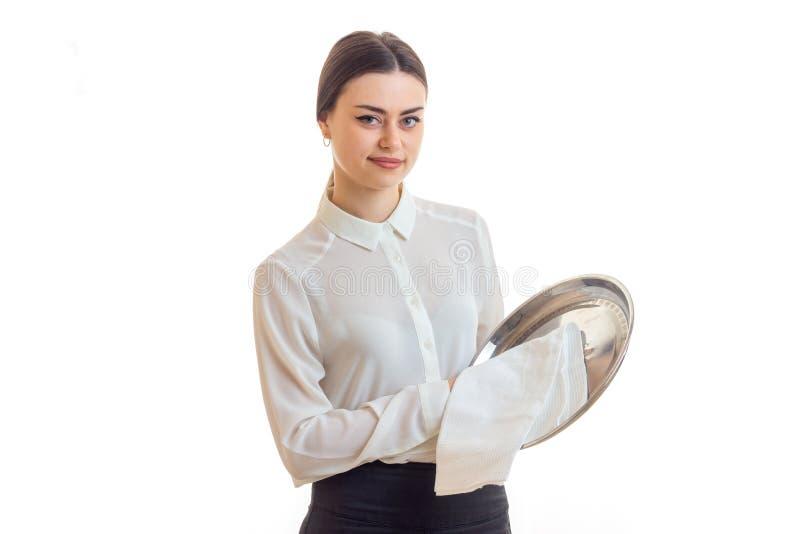 De vrij jonge serveerster maakt een zilveren trey en het bekijken de camera schoon stock afbeelding