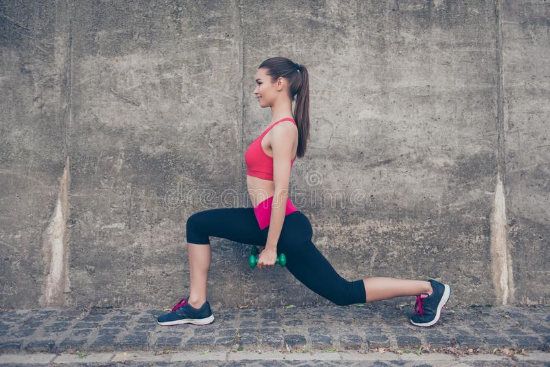 De vrij jonge slanke trainer rekt haar benen door exerci uit te doen stock afbeelding