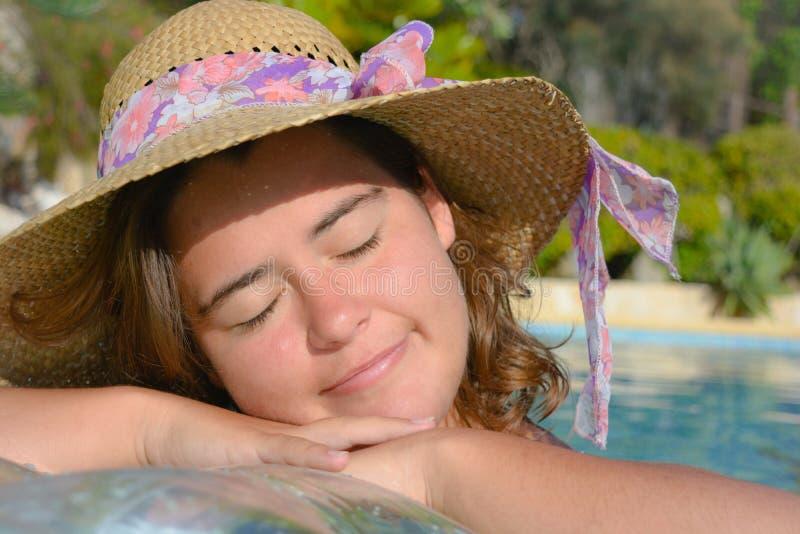 De vrij jonge vrouw die een hoed, ogen dragen sloot, ontspannen en gelukkig, in openlucht royalty-vrije stock foto