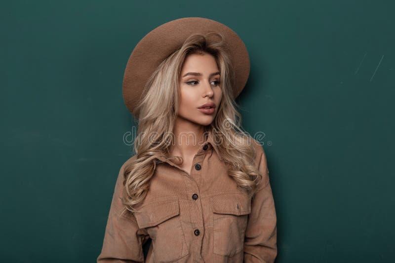 De vrij jonge vrouw in een elegante beige hoed in een modieus overhemd met blond krullend blond haar bevindt zich in de studio royalty-vrije stock afbeeldingen