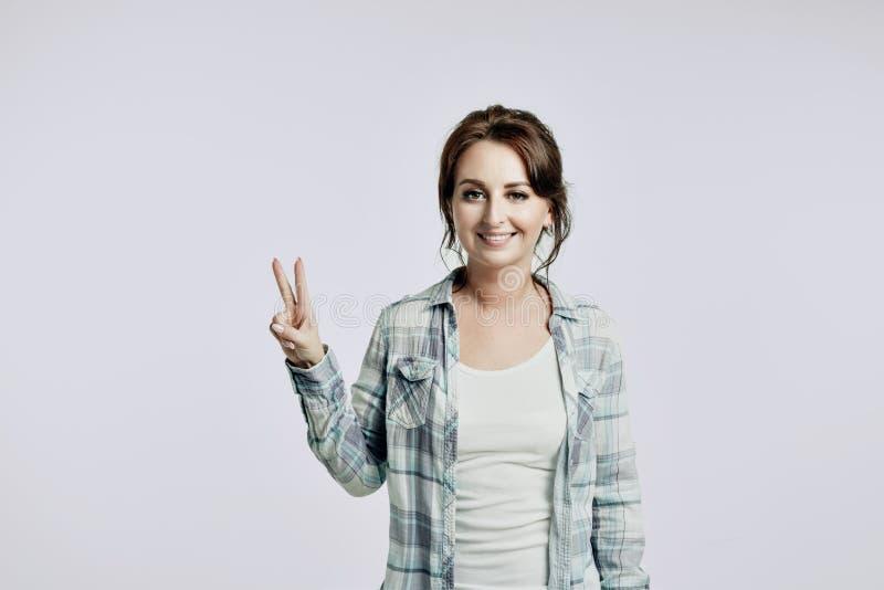 De vrij jonge vrouw in een wit overhemd en een lichtblauw geruit overhemd toont een teken van vrede stock afbeelding