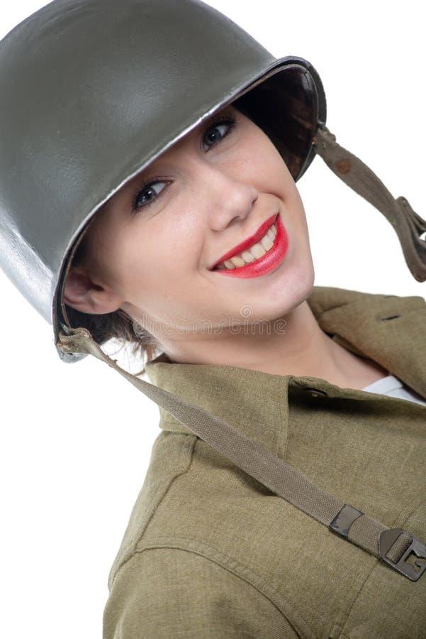 De vrij jonge vrouw kleedde zich in Amerikaanse militaire eenvormig van ww2 met M1-helm royalty-vrije stock afbeelding