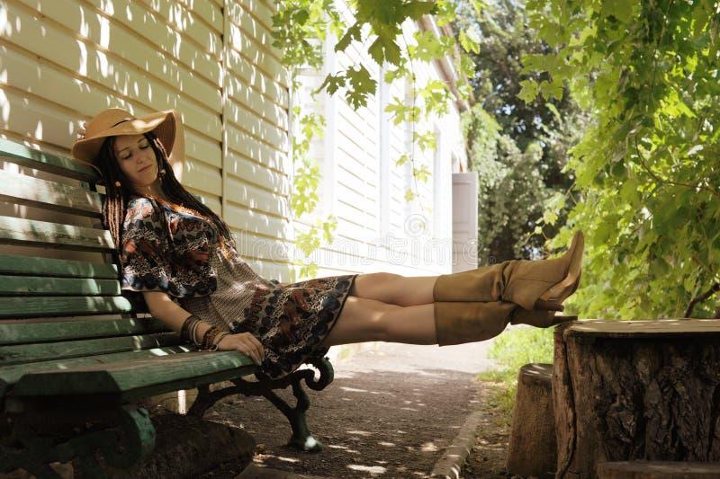 De vrij jonge vrouw met dreadlocks kleedde het rusten openlucht dichtbijgelegen haar huis op een bank royalty-vrije stock fotografie
