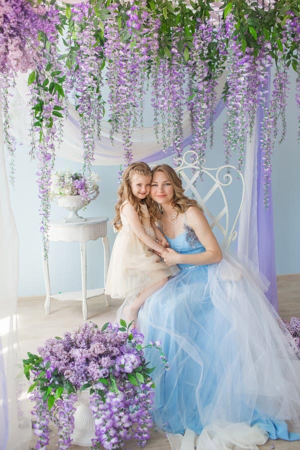 De vrij Jonge vrouw met haar weinig dochter zit in een studio verfraaide een sering bloeit royalty-vrije stock afbeeldingen