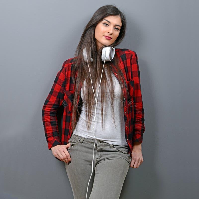 De vrij jonge vrouw met hoofdtelefoons geniet van de muziek die op grijze muur wordt geleund royalty-vrije stock afbeeldingen