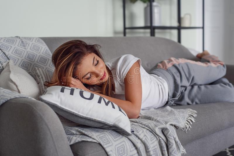 De vrij jonge vrouw met mooie glimlach ligt op grijze laag met hoofdkussens bij comfortabel huis Leuk meisje die rust hebben thui royalty-vrije stock foto