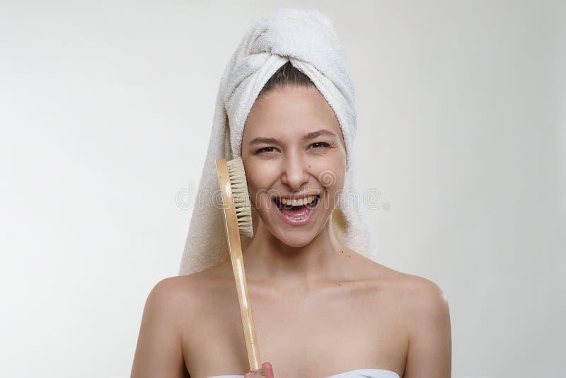 De vrij jonge vrouw met mooie verse huid en de prachtige glimlach in handdoek het stellen met een houten massage borstelen op wit stock fotografie
