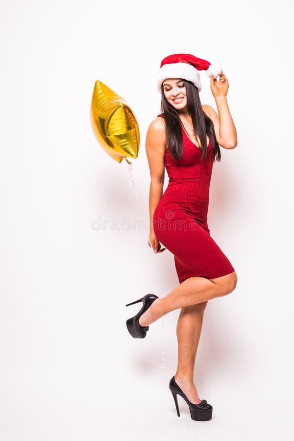De vrij jonge vrouw in rode kleding en santakerstmishoed met gouden ster vormde ballon stock foto's