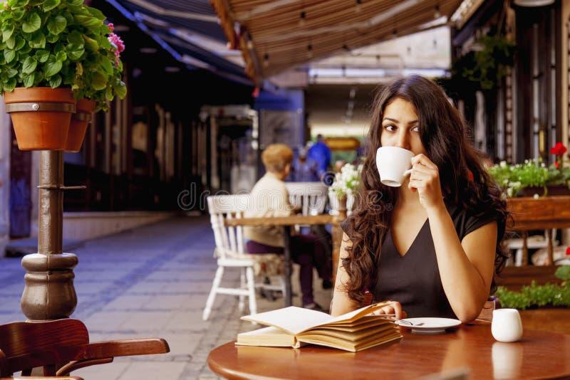 De vrij jonge vrouw rust in koffieterras en leest boek D stock foto's
