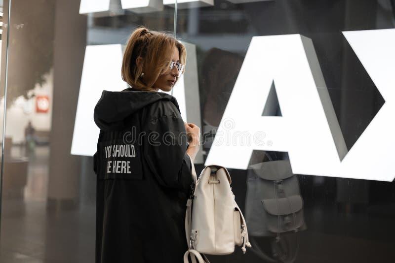 De in vrij jonge vrouw in uitstekende glazen in een modieuze regenjas met een modieuze witte leerrugzak rust binnen stock afbeeldingen