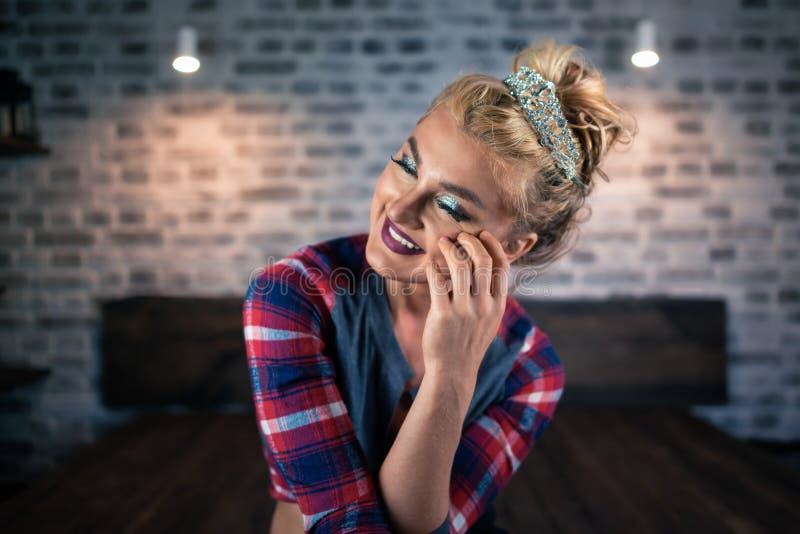 De vrij jonge vrouw zit op het bed in modieuze slaapkamer Russisch blondemeisje royalty-vrije stock foto's