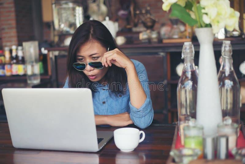 De vrij jonge zitting van de hipstervrouw in een koffie met haar laptop, lo stock afbeeldingen