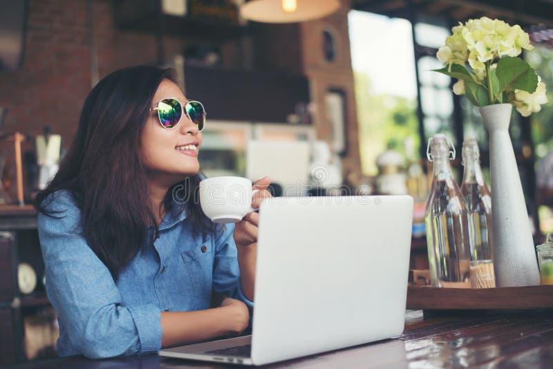 De vrij jonge zitting van de hipstervrouw in een koffie met haar laptop, lo stock foto's