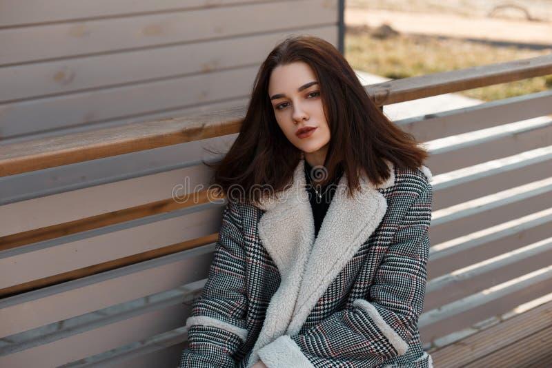 De vrij mooie jonge donkerbruine vrouw in een modieus plaidjasje met wit bont zit en ontspant op een bank in de stad royalty-vrije stock fotografie