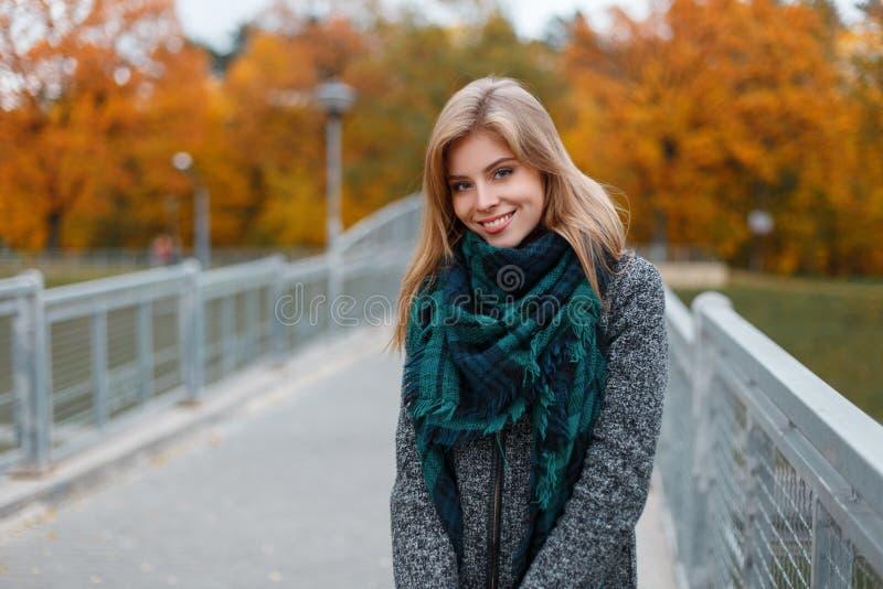 De vrij mooie jonge vrouw met een mooie glimlach in een modieuze grijze laag met een groene uitstekende sjaal loopt in openlucht royalty-vrije stock foto's