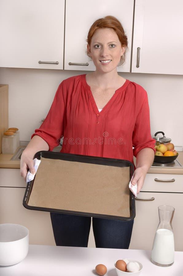 De vrij rode haired vrouw toont leeg bakseldienblad, vrije exemplaarruimte stock foto's