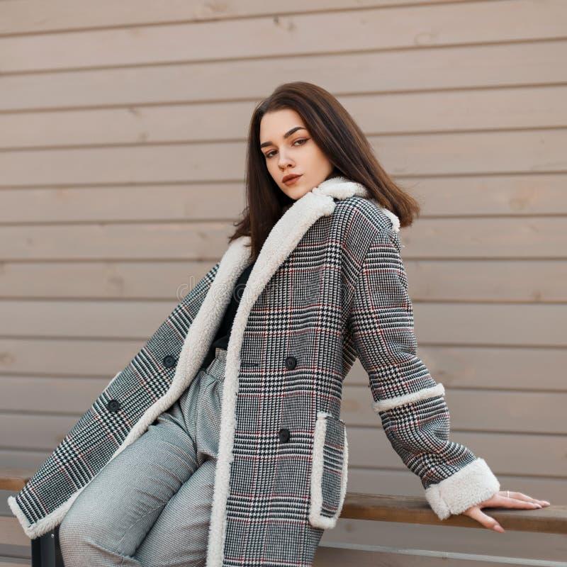 De vrij sexy jonge vrouw in een elegant geruit jasje in een overhemd in grijze uitstekende broek zit en ontspant op een de lented stock afbeelding