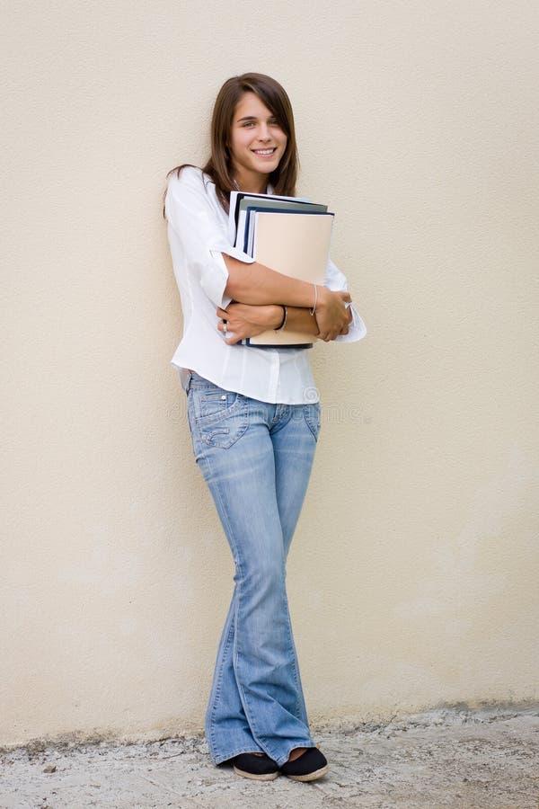 De vrij vrouwelijke boeken van de studentenholding in haar handen stock afbeelding