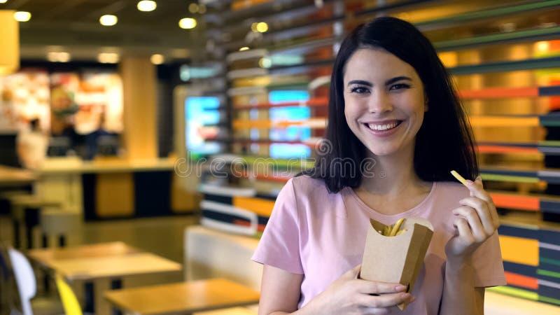 De vrij vrouwelijke holdingsfrieten die, snel voedselsnack, stelden klant tevreden glimlachen stock foto