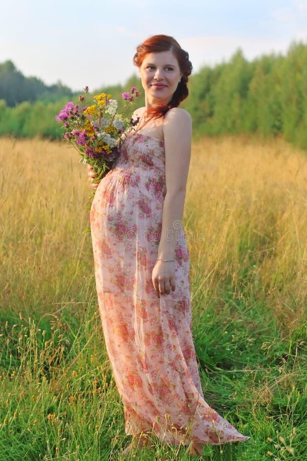 De vrij zwangere vrouw in kleding stelt met wilde bloemen bij s royalty-vrije stock foto's