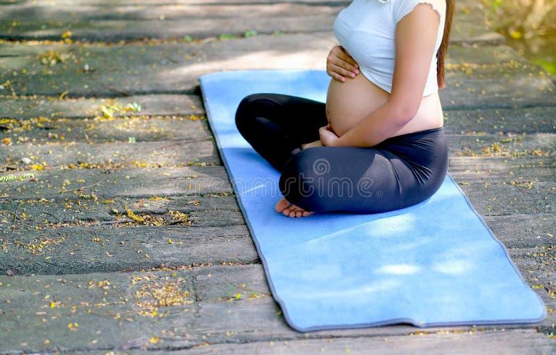 De vrij zwangere vrouw raakt haar buik en zit op blauwe mat over houten brug in de tuin met zacht licht in de ochtend royalty-vrije stock fotografie