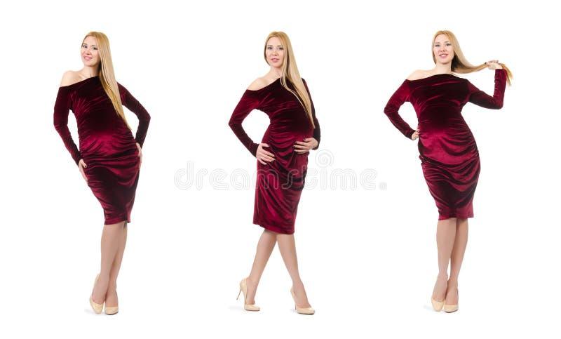 De vrij zwangere vrouw in rode die kleding op wit wordt ge?soleerd stock foto