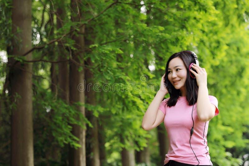 De vrije achteloze causual vrouw van het schoonheidsmeisje geniet van ontspant tijd in de zomer van de aardlente luisterend aan m stock fotografie