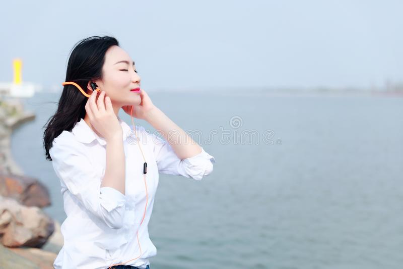 De vrije achteloze causual vrouw van het schoonheidsmeisje luistert aan muziek door strand de oceaanmeerrivier ontspant tijd in d stock foto
