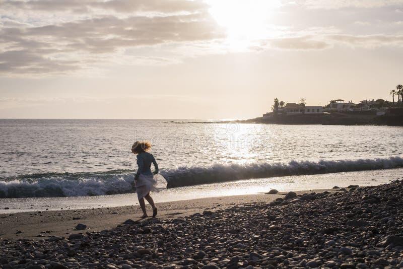 De vrijheid en de aardige vrouw dansen en hebben pret bij het strand op de kust genietend van de zomer en van de zonsondergang Vr royalty-vrije stock foto