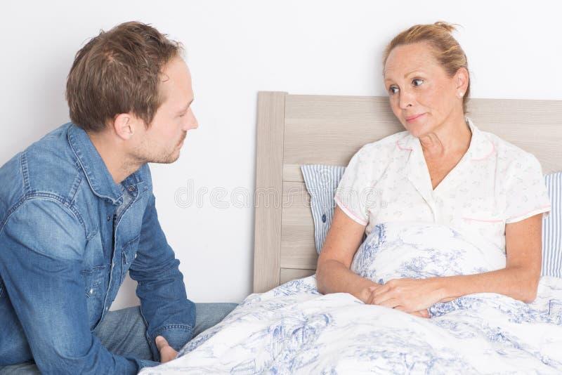 De vrijwilliger behandelt bejaarde in bed stock fotografie